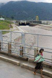 A woman woman walks past the Nam Theun 2 power station in Khammouane province, Laos