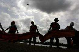 Contract workers unload oil booms