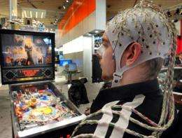Crowds gathered round a man sitting at a pinball table, wearing a cap covered in electrodes attached to his head