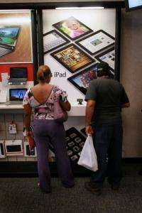 Customers check out the iPads on display at a store in Coral Gables, Florida