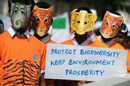 """Indian students hold a 'protect biodiversity; keep environment; prosperity"""" poster at a World Environment Day rally"""