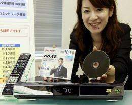 Japanese electronics giant Sharp employee displays the BDXL standard Blu-ray disc and its recorder