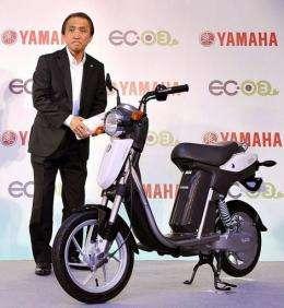 Japan's Yamaha Motor President Hiroyuki Yanagi stands next to the company's new electric commuter vehicle EC-03