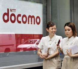 Pedestrians use their mobile phones as they walk past a NTT docomo shop