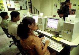 People browse the net at a cyber cafe in Calcutta