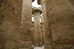 Tourists explore stone columns decorated with hieroglyphs at the Karnak temple site in Luxor