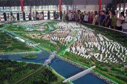 "Visitors look at a model of an ""eco-city"""
