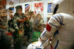 "Visitors take photos during an exhibition on ""China's First Spacewalk Mission"" at the Hong Kong Science Museum"