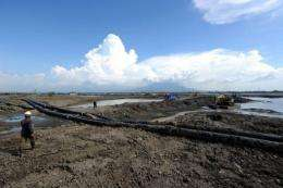 Workers attempt to control the flow of mud from the Lapindo mud volcano