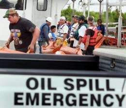 Workers load oil booms onto a boat as the effort continues to try and contain the massive oil spill