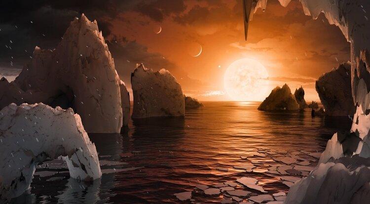 Esta concepção artística mostra a eterna alvorada em TRAPPIST-1f, numa área que poderia ser habitável. No céu, veem-se outros mundos bem próximos, 1e (crescente menor), 1d (crescente maior) e 1c (pontinho brilhante junto ao sol).