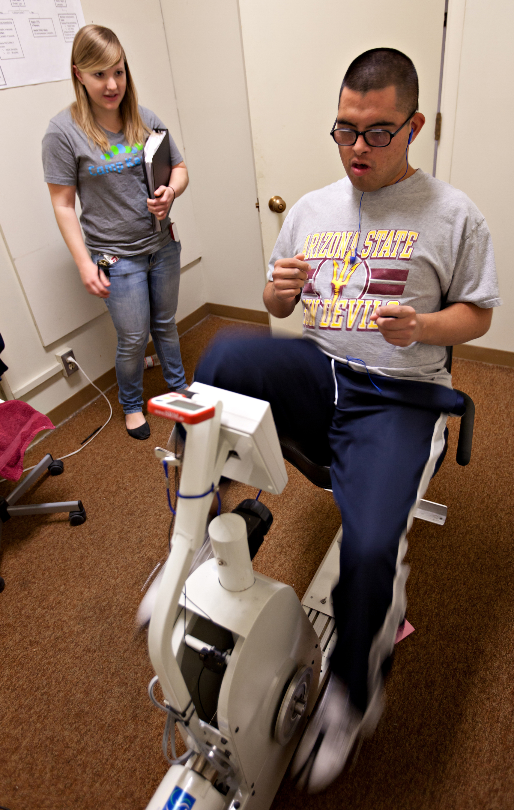 Down syndrome and physical therapy - Marcus Santellan Exercises On A Motorized Bike While Katy Lichtsinn An Asu Kinesiology Senior Encourages Him Credit Tom Story
