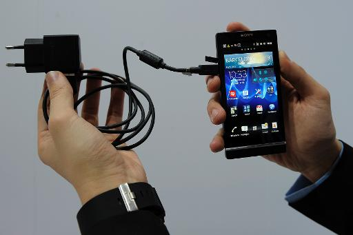 Man Displays Universal Charger Plugged In A Mobile Phone During Presentation At The World Congress On February 28 2012 Barcelona Spain