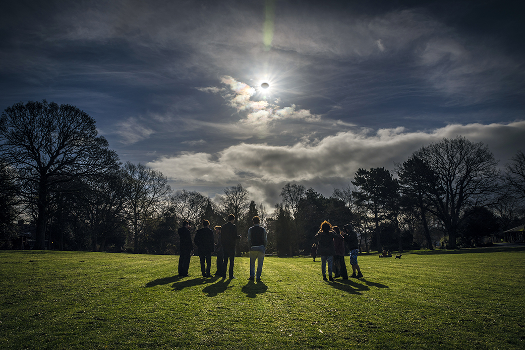 People watch a partial eclipse in Belfast Northern Ireland