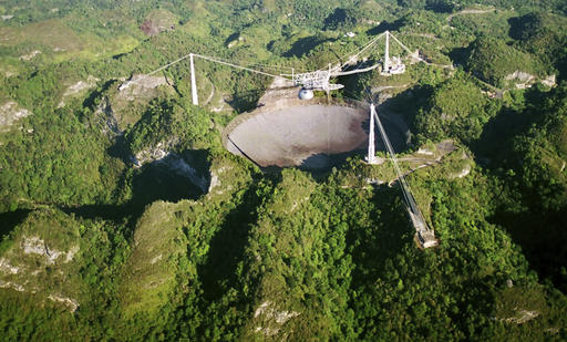 In this March 26, 2003, file photo, the world's largest radio telescope is seen from the air, at the Arecibo Observatory, in Puerto Rico. The future of one of the world's largest single-dish radio telescopes has been called into question after the U.S. National Science Foundation announced it was formally seeking someone to operate the Arecibo Observatory in Puerto Rico. The Wednesday, Jan 25, 2017, announcement comes as the federal agency runs out of funds to support the observatory. (AP Photo/ Tomas van Houtryve, File) Read more at: https://phys.org/news/2017-01-future-giant-radio-telescope-puerto.html#jCp